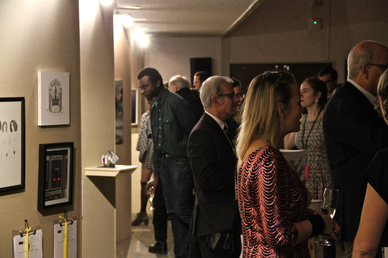People admiring artwork in the silent auction