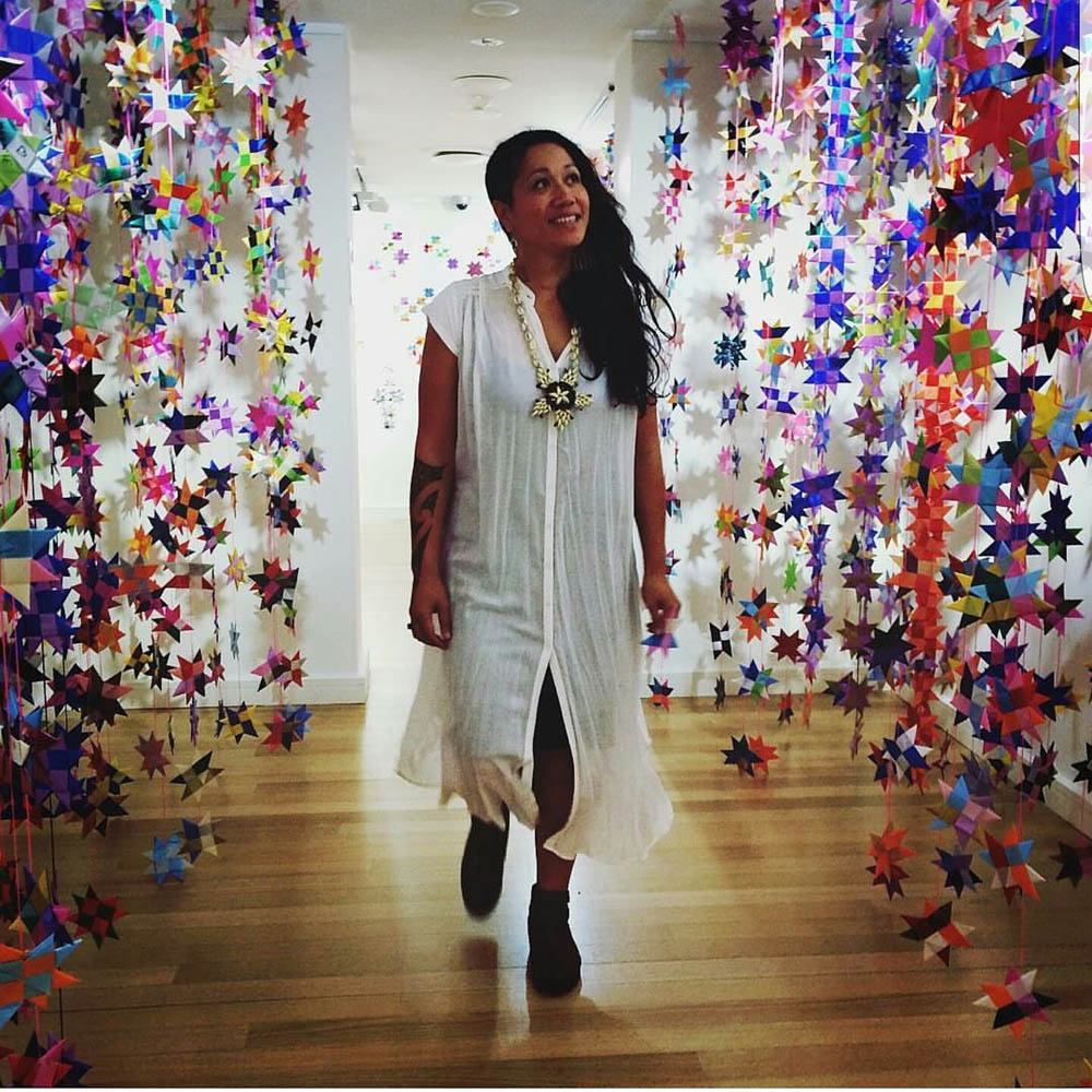 Maryann Talia Pau, standing with an installation of stars.