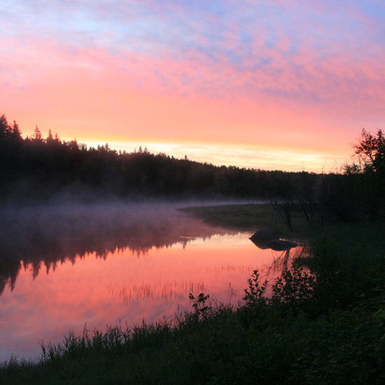 Image of sunrise over Bannock with reflection on water.