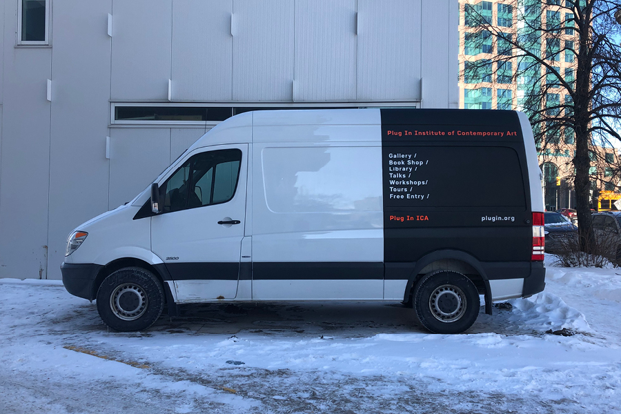 Tall white van with black advertising at back.
