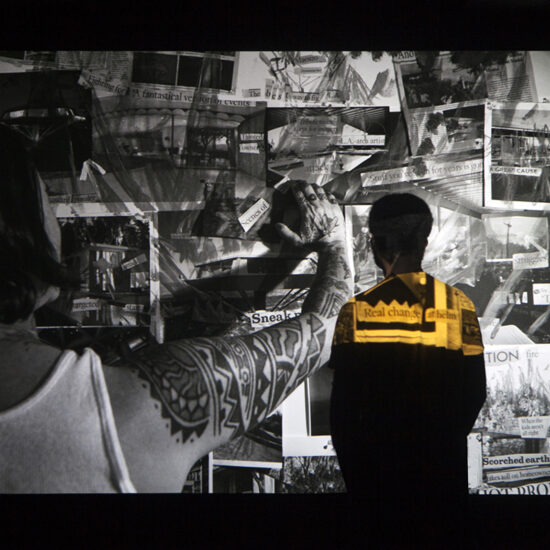 Viewer in yellow shirt standing in front of a scene from the Modernist.