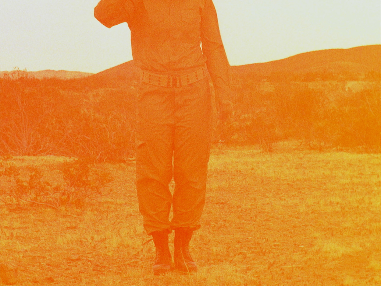 Legs of person in army uniform standing in desert with hills behind. Image is tinted orange.