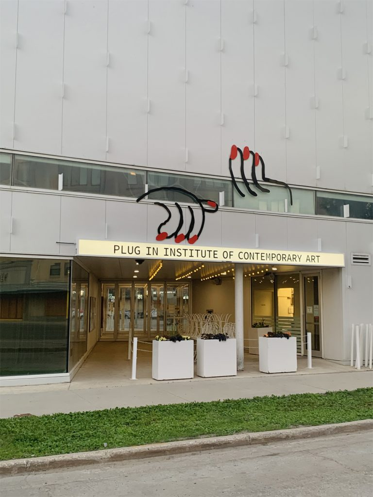 Two manicured hands reach out of the windows of the Buhler building above an illuminated Plug In ICA sign